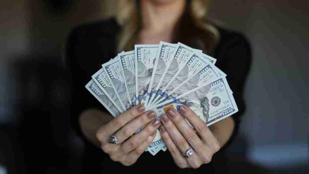 How to get a flight attendant job great pay woman holding hundred dollar bills